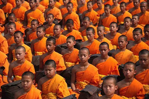 Group of young buddhists monks meditating
