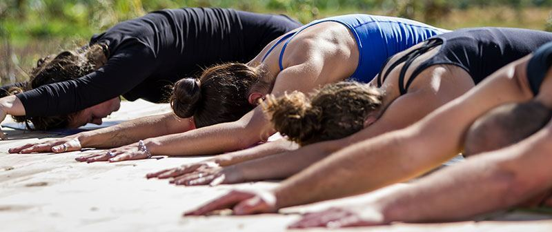 Group of women doing yoga at the beach